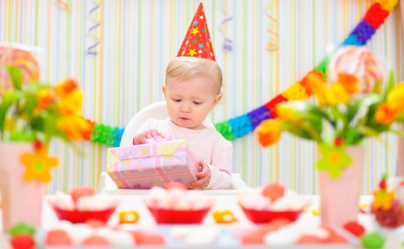 Baby der åbner en gave på sin 1-års fødselsdag