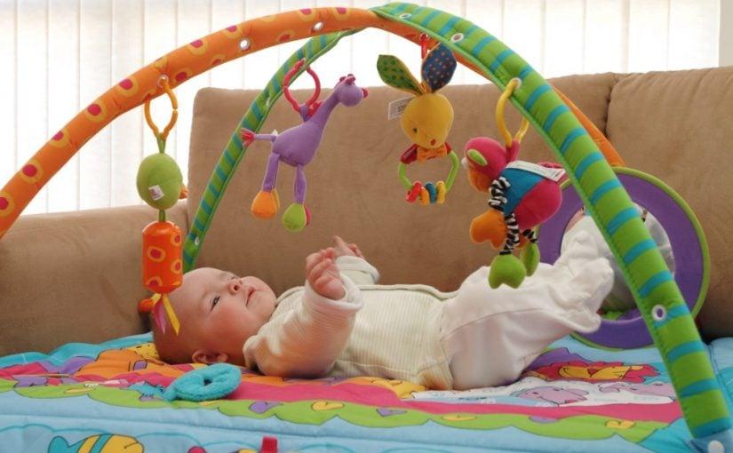 Baby der leger på aktivitetstæppe