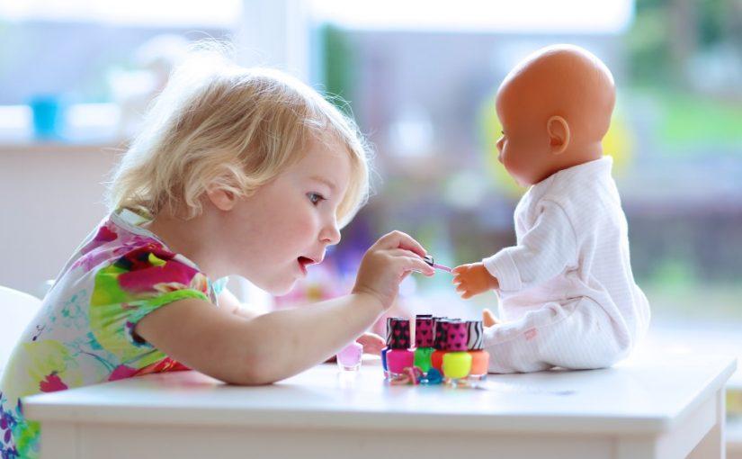 Pige der leger med sin dukke
